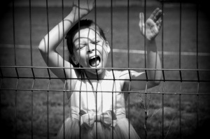 Girl against a fence screaming