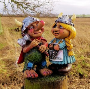 male and female nordic gnomes on a tree truk